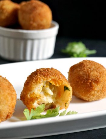 3 Butternut squash risotto balls on a white plate with a rameskin of more risotto balls in the background