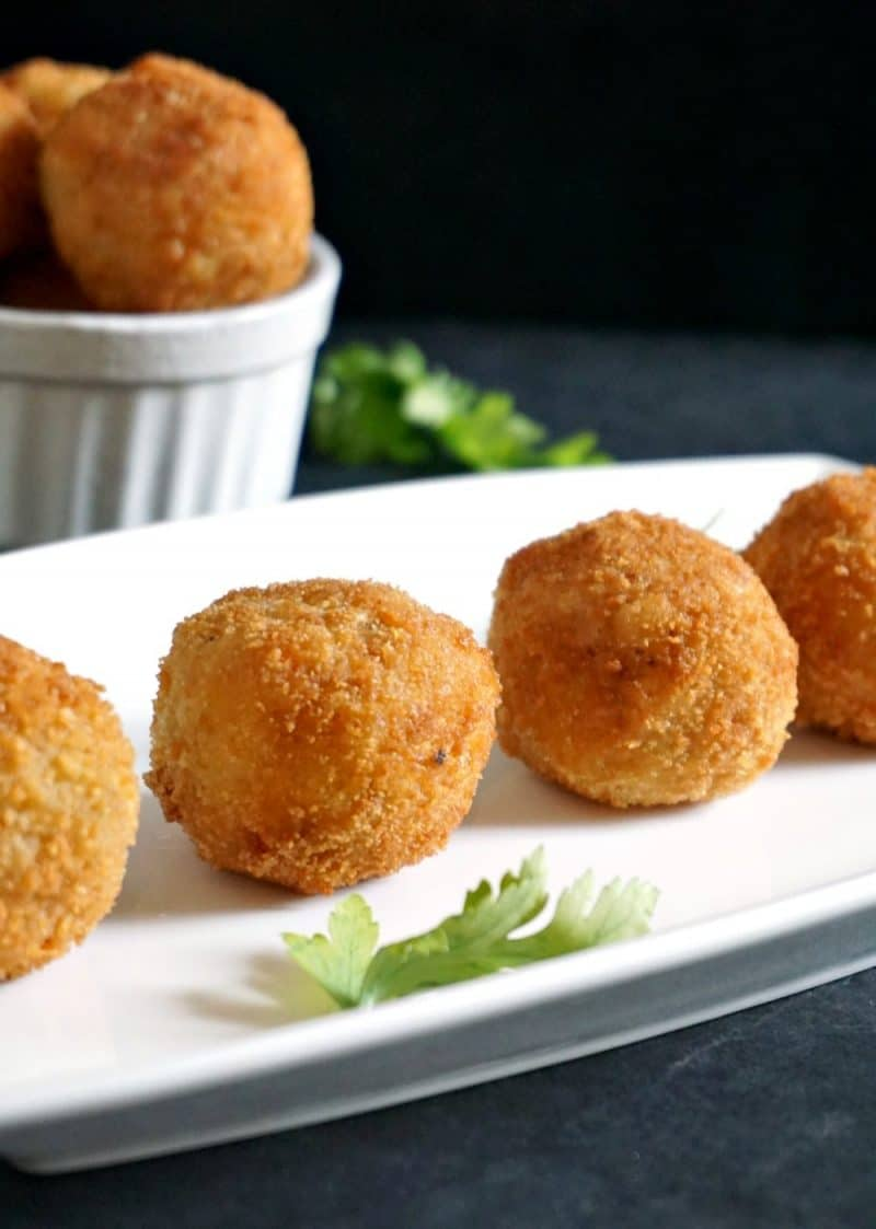 4 risotto balls arranged on a white rectangle plate with other risotto balls in a small bowl