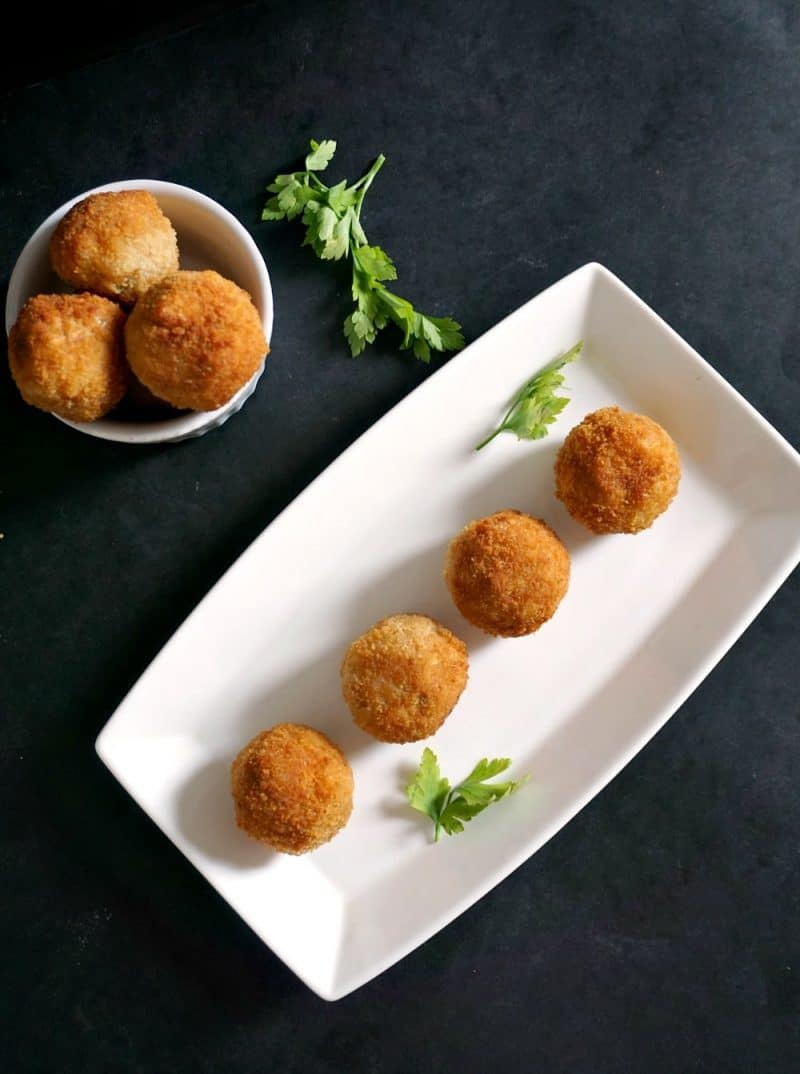 4 arancini on a white rectangle plate with a small white bowl with 3 arancini in