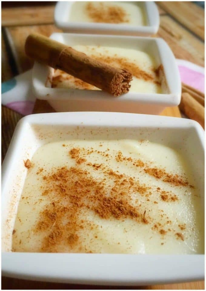 3 small white bowls of semolina pudding topped with cinnamon