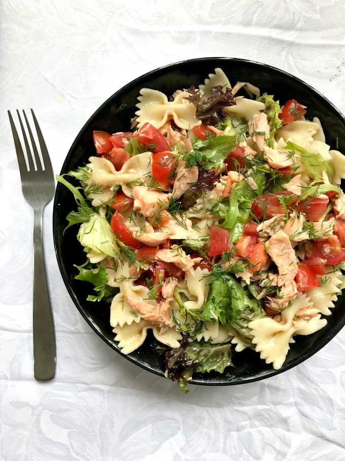 Overhead shoot of a black bowl of pasta salad with salmon with a fork necxt to it.