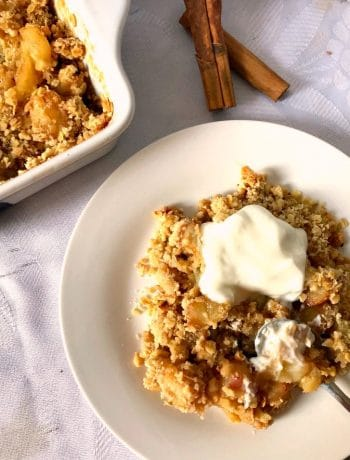 Overhead shoot of a white plate with peach crisp, an dish with peach crisp and 2 cinnamon sticks on the side