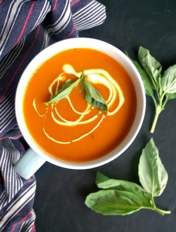 Overhead shoot of a bowl of Light Roasted Tomato and Red Pepper Soup garnished with basil leaves