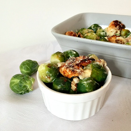 A small white bowl of Brussels Sprout Casserole next to a baking dish with casserole and two brussels sprouts next to it