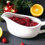 A white bowl of homemade cranberry sauce with orange juice, fresh cranberries scattered around the bowl and a slice of orange next to a Christmas tree