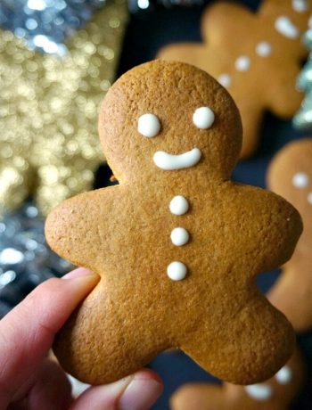 A hand holding a gingerbread man cookie