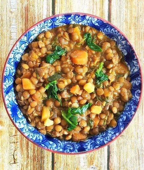 Overhead shot of a blue bowl of brown lentil soup