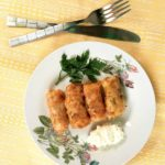 Overhead shoot of a plate with 4 suffed cabbage rolls with a dollop of sour cream on the side and parsley leaves