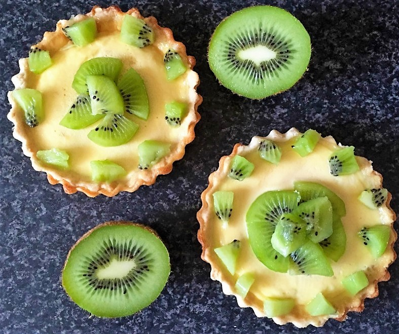 Overhead shot of two kiwi tartlets and 2 halves of kiwi