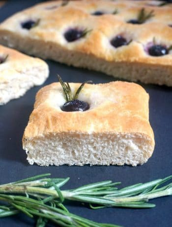 A slice of focaccia with rosemary and a grape, and more focaccia bread in the background