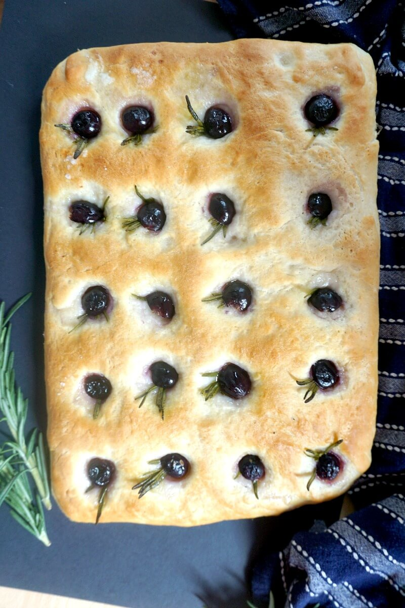 Overhead view of a focaccia topped with rosemary and grapes