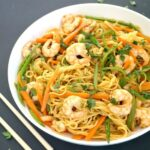 A white plate with shrimp stir-fry with noodles