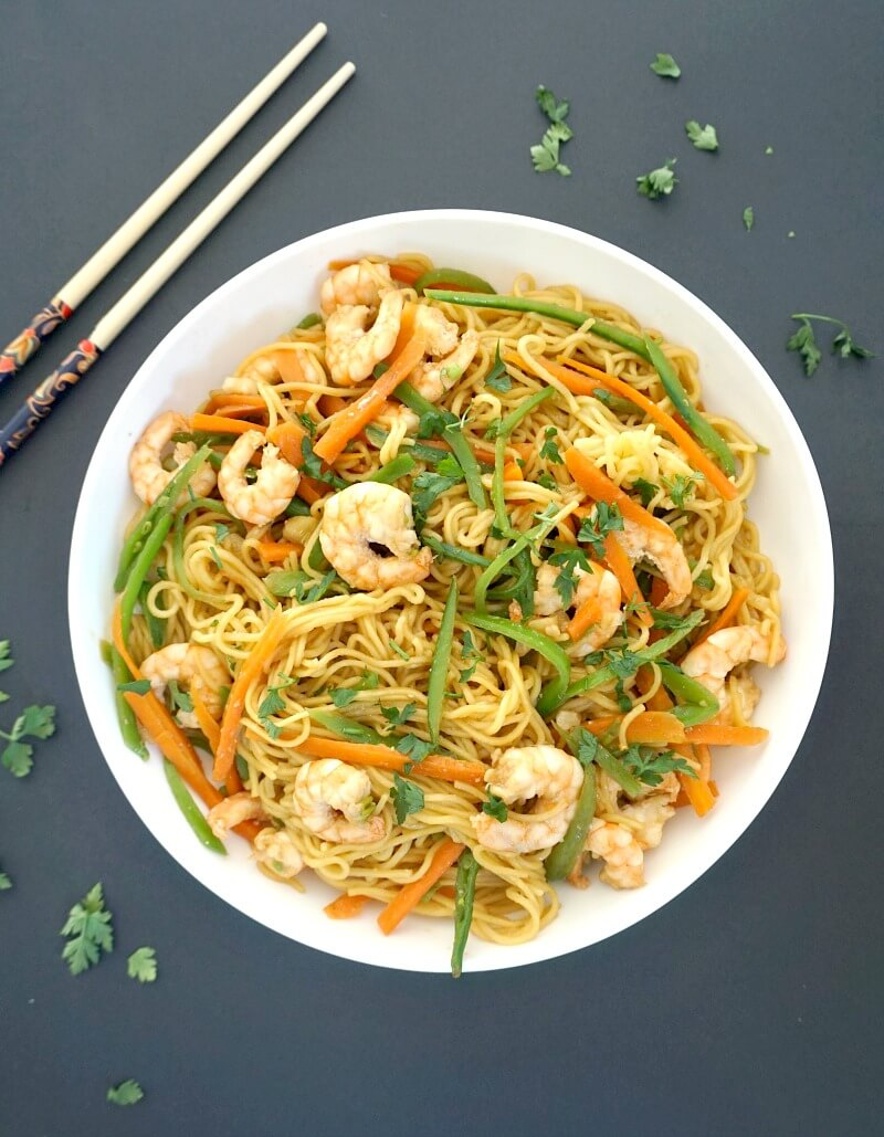 Overhead shoot of a white plate with shrimp stir fry with noodles and chopsticks on the side