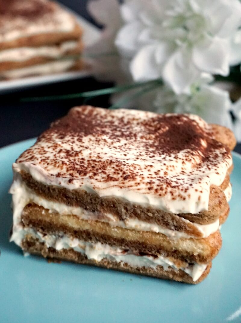 A slice of tiramisu on a light blue plate