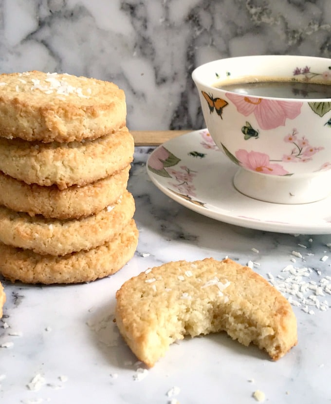 A stack of coconut shortbread cookies next to a cup of coffee and half of a coconut shortread cookie
