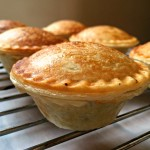A close shot of a mini mushroom pie on an oven rack with other pies in the background