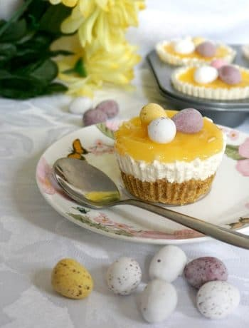 A mini lemon cheesecake on a small plate with a teaspoon next to it, easter eggs scattered around, and yellow flowers and a tray of mini lemon cheesecakes in the background