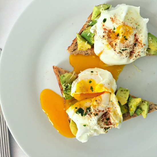 Overhead shoot of a white plate with 2 bread slices topped with avocado and poached eggs