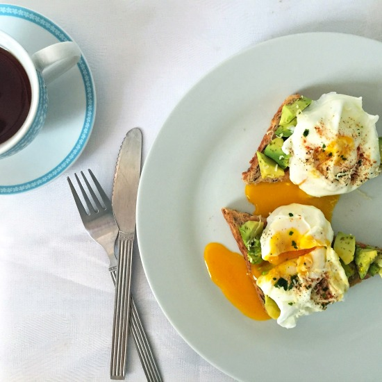Overhead shot of a white plate with 2 toasts topped with chopped avocados and poached eggs, fork and knife on the side and a cup of tea