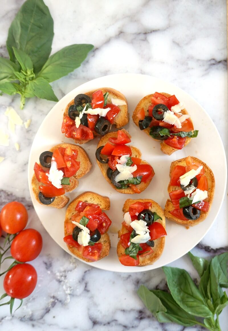 Overhead shot of a white plate with 7 tomato bruschetta, a few basil leaves and cherry tomatoes on the side