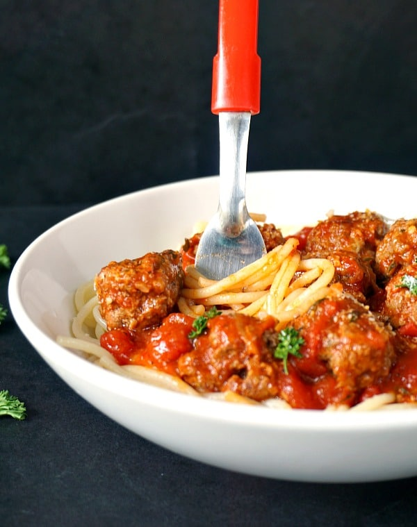 A white plate of spaghetti with meatballs with a fork swirling the spaghetti