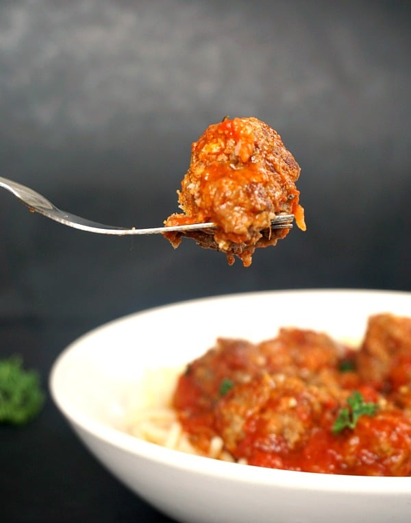 A fork with a meatball over a white plate of spaghetti with meatballs