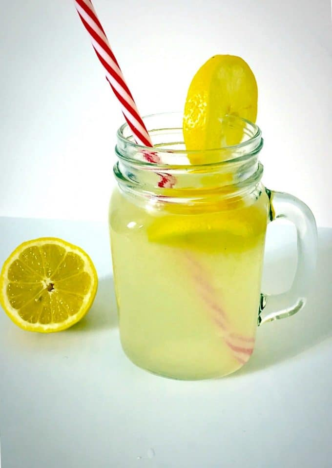 A mason jar of honey-sweetened lemonade with half a lemon next to it