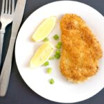 Overhead shot of a chicken schnitzel on a white plate with 2 lemon wedges, chopped spring onions and cutlery on the side
