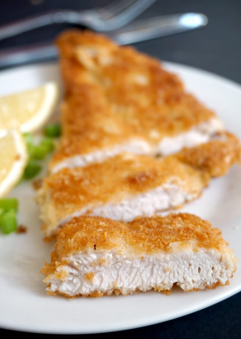 A sliced chicken schnitzel on a white plate