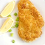 Overhead shot of a chicken schnitel on a white plate with 2 lemon wedges and chopped green onions
