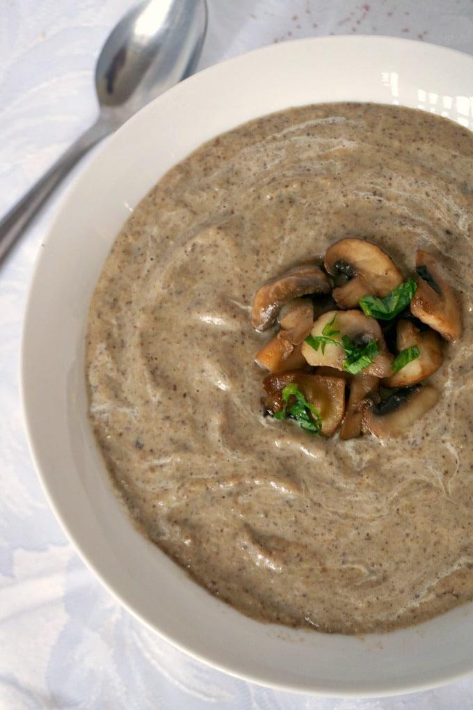 Overhead shot of a white bowl of cream of mushroom soup