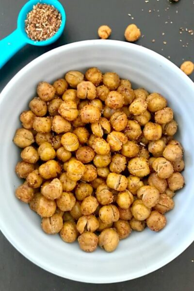 Overhead shoot of a small bowl of crnchy roasted chickepeas, and a teaspoon of spices on the side