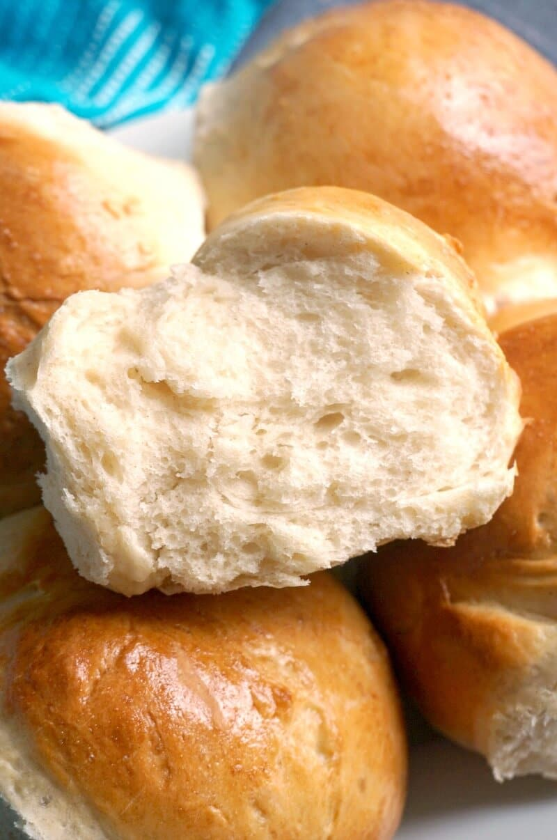 Close-up shoot of half a dinner roll on top of other rolls