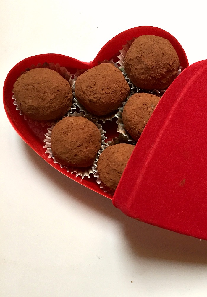 A red-heart shaped box with 6 coconnut truffles coated in cocoa powder