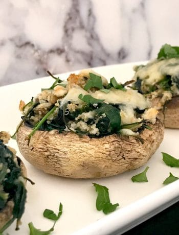 3 Spinach-Stuffed Mushrooms on a white serving plate