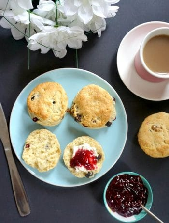 Overehead view of a blue plate with 4 british scones, a cup of tea on the side and a small bowl of jam