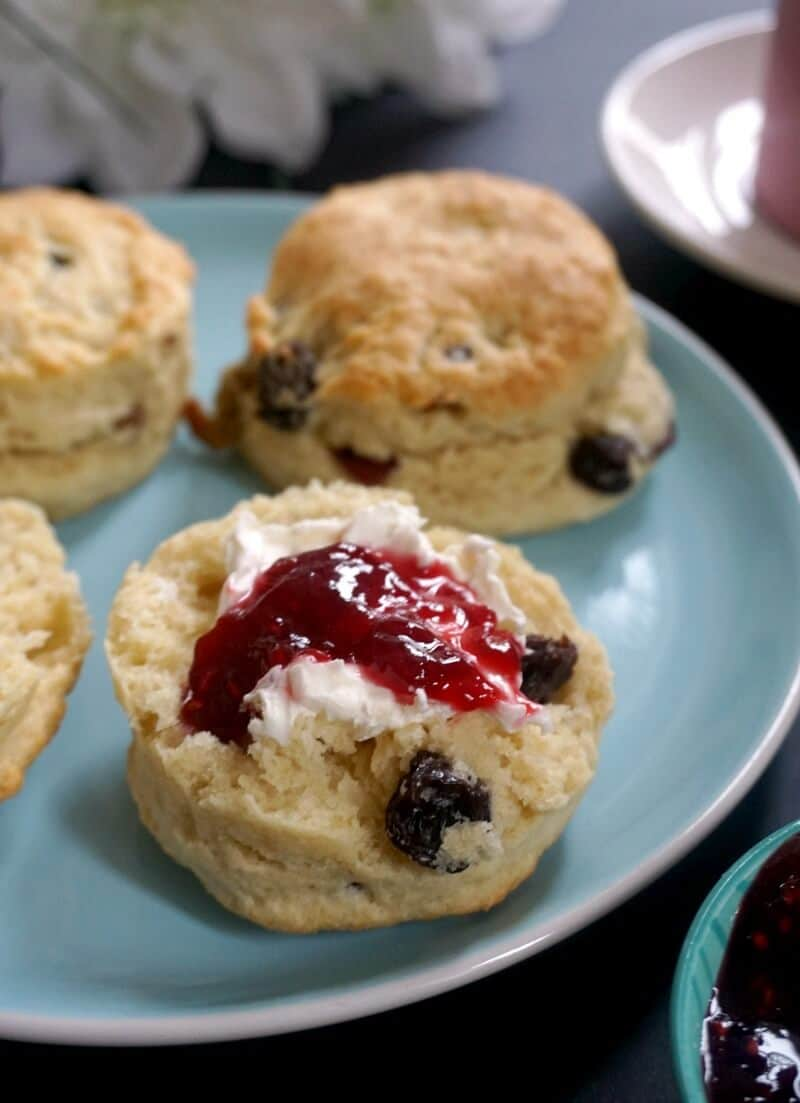 Half a british scone topped with clotted cream and ja, with other 3 scones around on the same plate
