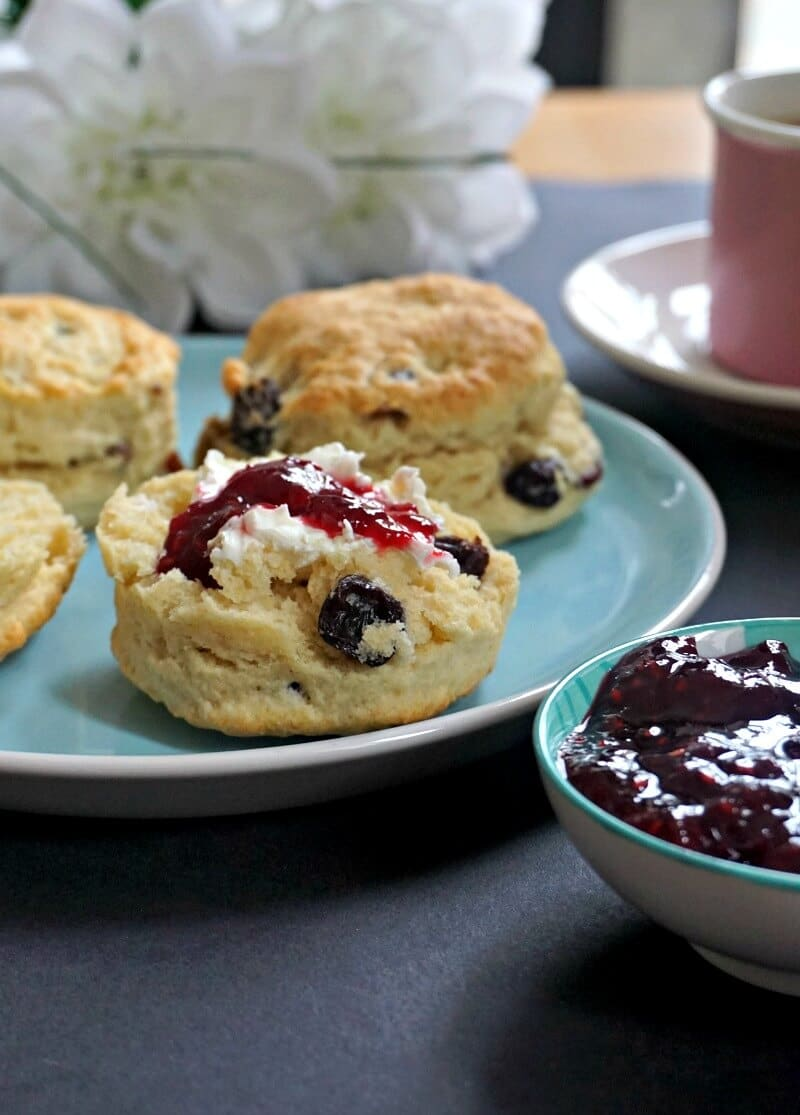 A blue plate with 4 english scones, one topped with cream and jam