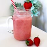 A jar of Strawberry Banana Coconut Milk Smoothie, with 2 strawberries on the side and one topping the jar