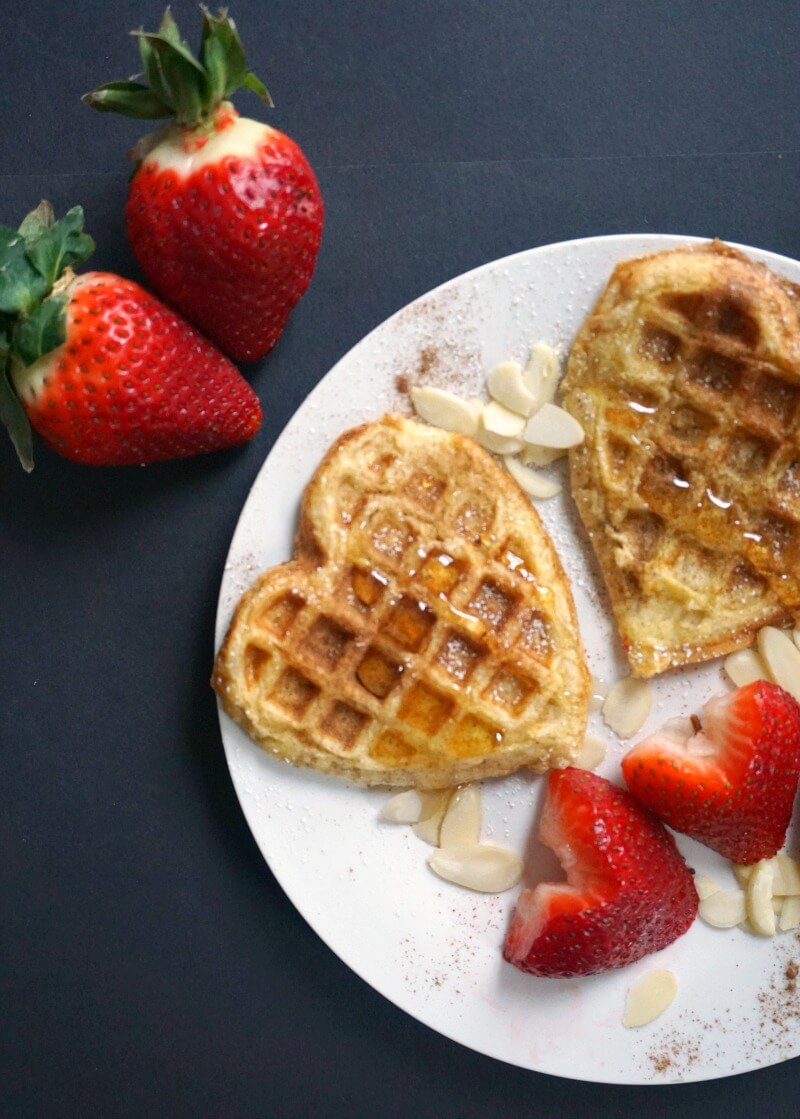 Overhead shoot of a white plate with 2 french toast waffles and 4 strawberries