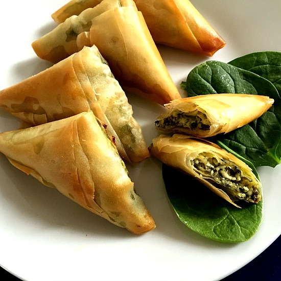 6 spanakopita triangles on a white plate with 3 fresh baby spinach leaves