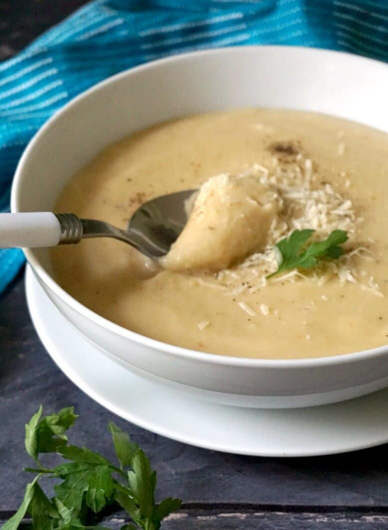 A white bowl of roasted parsnip soup with a spoon in it