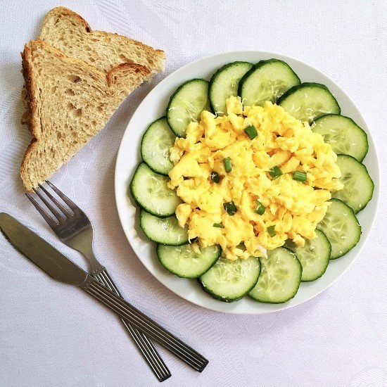 Overhead shot of a white plate with cucumber slices, scrambled eggs, and 2 slices of toast with a fork and knife on the side of the plate