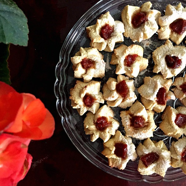 Overhead shot of a plate of shortbread thumbprint cookies with quince jam