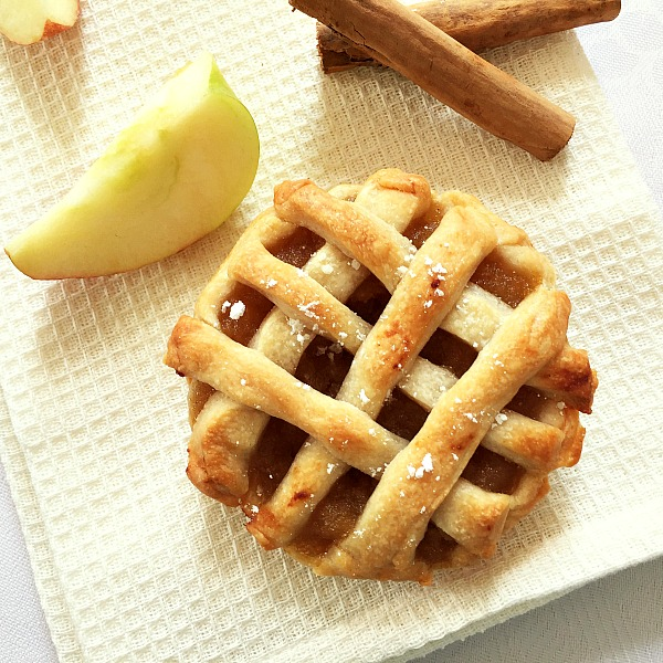 Overhead shot of a mini apple pie on a white table cloth with an apple wedge next to it and two cinnmaon sticks