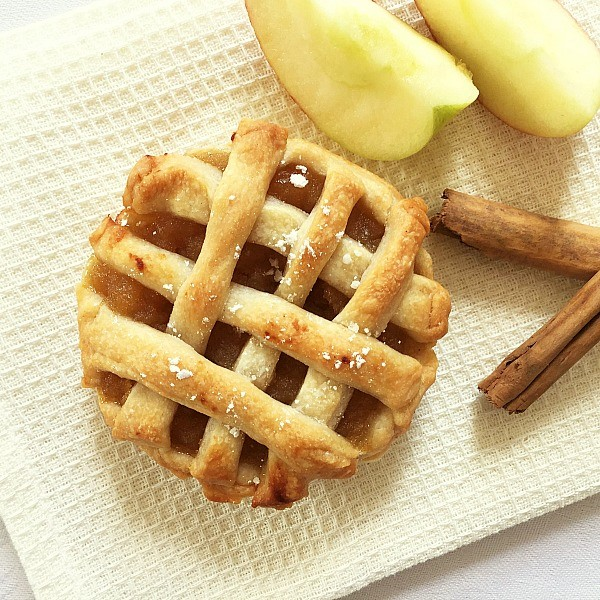 Overhead photo of a mini apple pie on a white cloth with two wedges of apples and two cinnamon sticks next to it