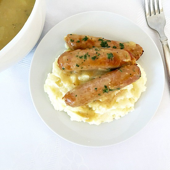 Overhead photo of a white plate of mashed potatoes and sausages, with a fork next to it