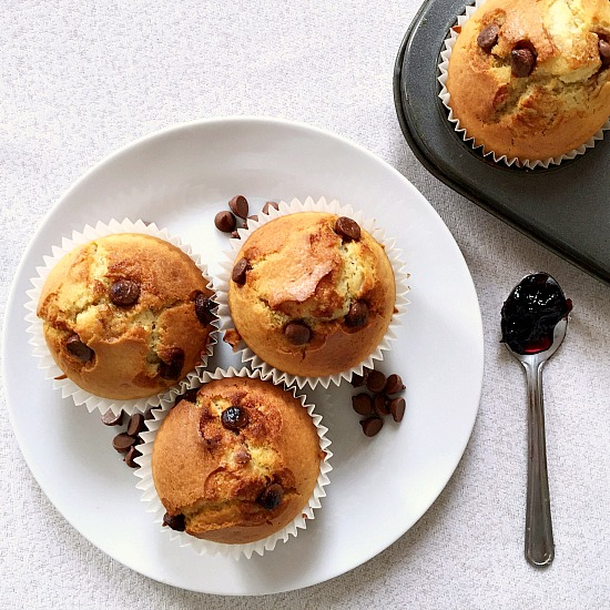 Overhead shot of a white plate with 3 homemade chocolate chip muffins and a teaspoon with cherry jam on the side