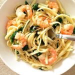 A white bowl of pasta with shrimp(prawn) and spinach