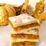 a stack of 3 pumpkin squares with a pumpkin in the background and dry leaves
